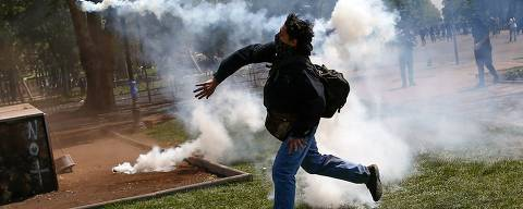 TOPSHOT - Demonstrators clash with riot police during protests in Santiago, on October 20, 2019. - Fresh clashes broke out in Chile's capital Santiago on Sunday after two people died when a supermarket was torched overnight as violent protests sparked by anger over economic conditions and social inequality raged into a third day. (Photo by Pablo VERA / AFP)