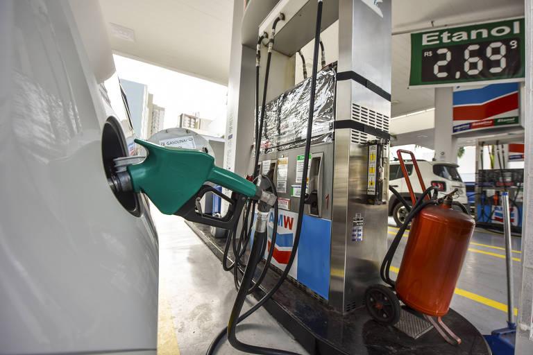A foto mostra uma bomba de combustível com a mangueira abastecendo um carro branco. Acima, uma placa mostra que o preço do etanol no posto estava em R$ 2,69.