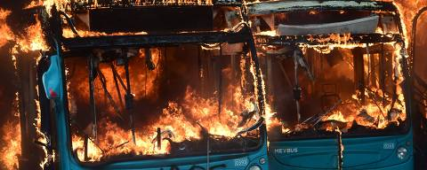 A bus burns down during clashes between protesters and the riot police at Plaza de Maipu in Santiago, on October 19, 2019. - Chile's president declared a state of emergency in Santiago Friday night and gave the military responsibility for security after a day of violent protests over an increase in the price of metro tickets. (Photo by Martin BERNETTI / AFP)
