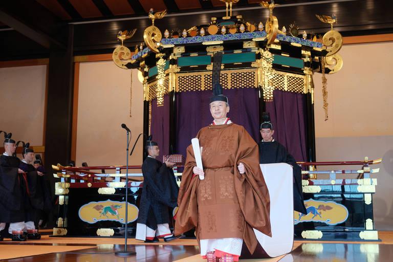 Com veste típica marrom, Naruhito caminha com um papel na mão. Atrás, duas pessoas carregam cauda branca da sua vestimenta