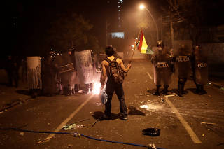 A demonstrator holds a flag while standing in front of police during a protest in La Paz