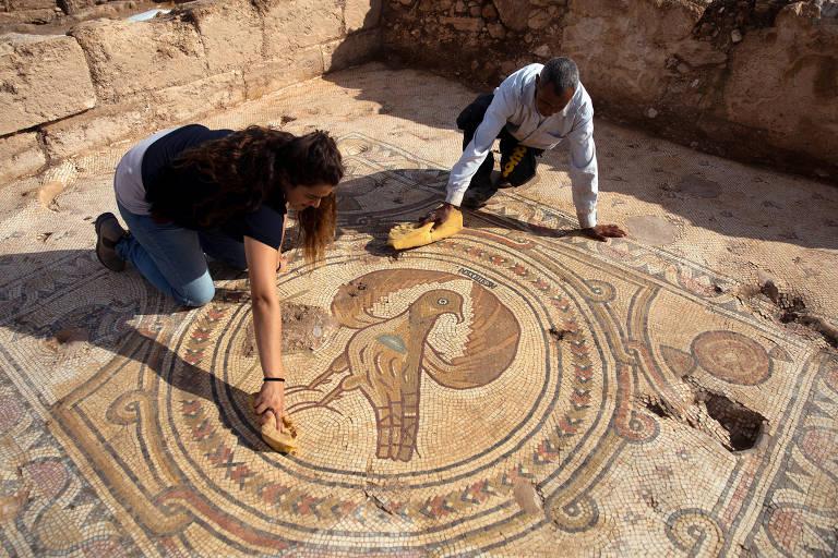 Duas pessoas ajoelhadas no chão limpam piso de mosaico