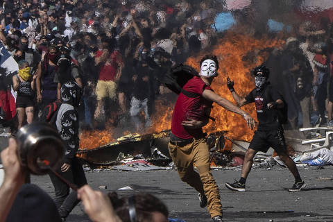 TOPSHOT - People demonstrate at Plaza Italia on the fifth straight day of street violence which erupted over a now suspended hike in metro ticket prices, in Santiago on October 22, 2019. - President Sebastian Pinera convened a meeting with leaders of Chile's political parties on Tuesday in the hope of finding a way to end street violence that has claimed 15 lives, as anti-government campaigners threatened new protests. (Photo by Pedro UGARTE / AFP)