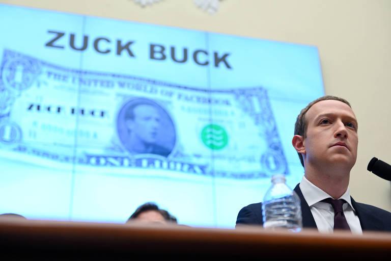 """Mark Zuckerberg depõe em frente a uma projeção de um """"Zuck Buck"""", paródia crítica a criptomoeda libra, do Facebook"""
