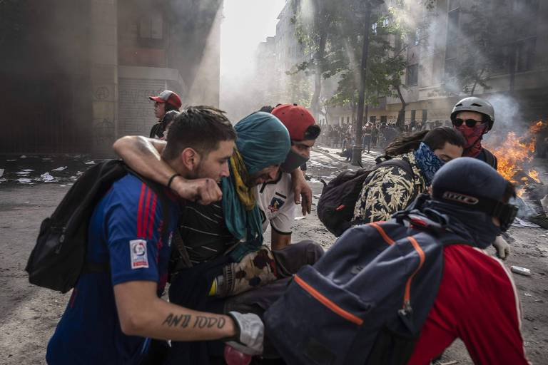 Torcedor da Universidad de Chile (de azul) e outro do Colo-Colo (de branco) carregam manifestante
