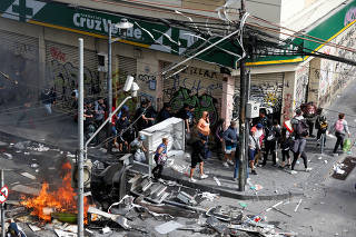 People walk towards a pharmacy during clashes in Valparaiso