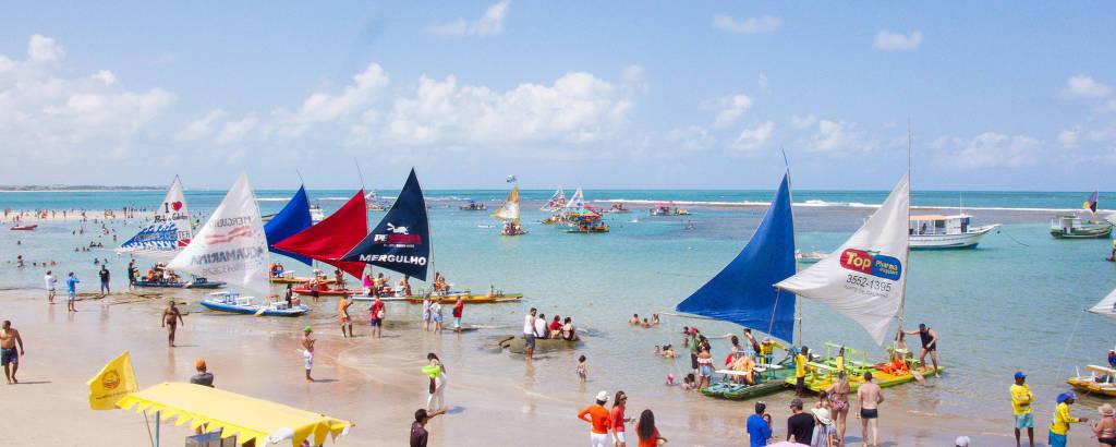 Pessoas em praia com água verde-clara