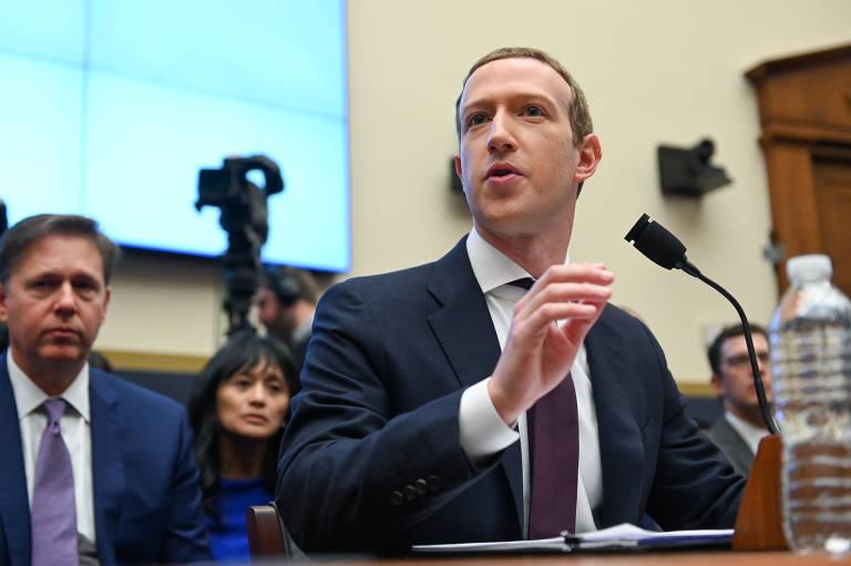 sentado, Mark Zuckerberg fala ao microfone