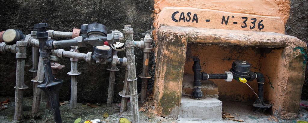 Emaranhado de canos e torneiras em calçada ao lado de um muro com um nicho para um registro, pintado de laranja, onde se lê CASA NÚMERO 336
