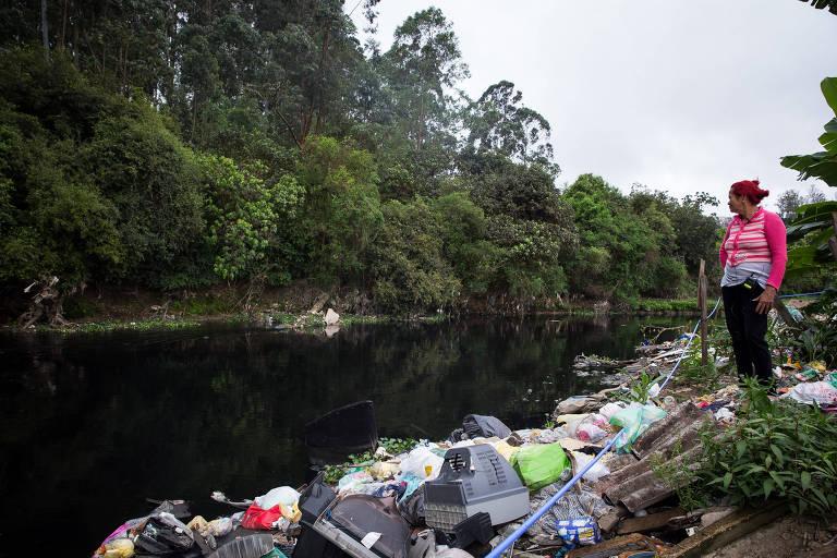 Maria Auxiliadora Silva, 58, mostra o entorno da comunidade Chácara Três Meninas no Jardim Helena, onde vive, na periferia de São Paulo