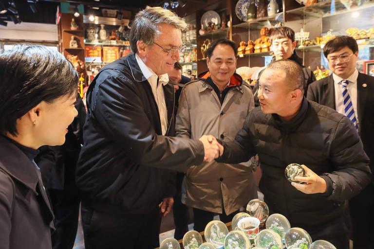 O presidente da República, Jair Bolsonaro, recebe uma lembrança de artesão chinês durante visita ao país