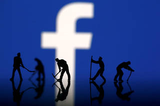 FILE PHOTO: Figurines are seen in front of the Facebook logo in this illustration