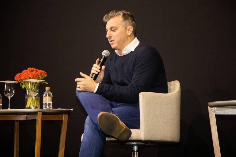 Luciano está sentado em uma cadeira, de pernas cruzas e com um microfone na mão; à sua esquerda há uma mesinha com flores e água