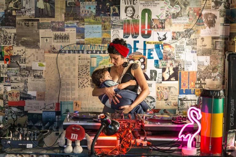 Atrás das pick ups (equipamento de áudio de djs) uma mulher amamenta um menino de aproximadamente 2 anos. Na parede ao fundo, diversos recortes de jornais, incluindo cruzadinhas, fotos de natureza, bandas e uma foto de Marielle Franco sorrindo