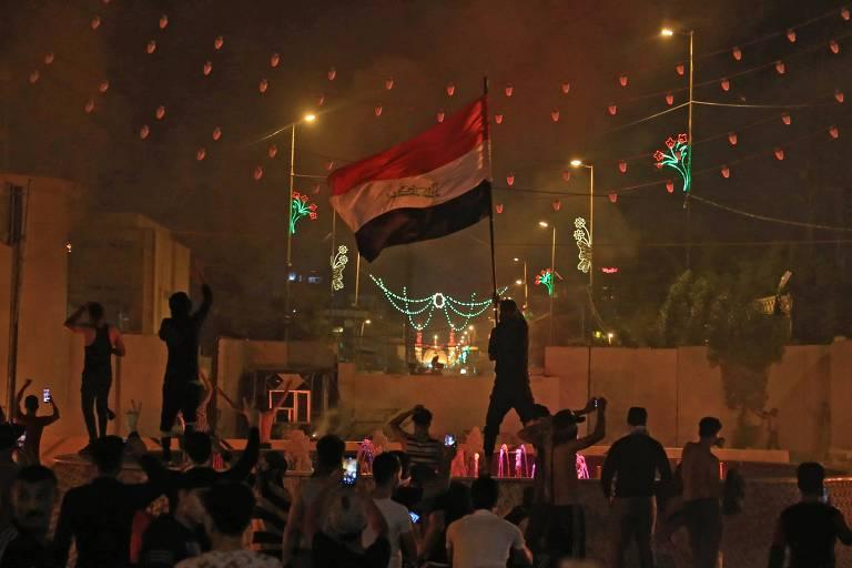 Manifestante ergue a bandeira do Iraque durante manifestação em Karbala, no sul do país