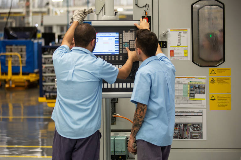Homens vestidos de azul trabalham com computador