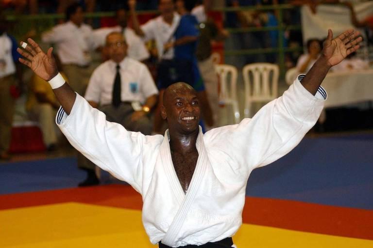 No centro do tatame, judoca levanta as mãos para o alto, em comemoração