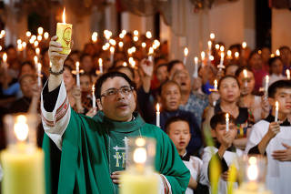 Catholic priest Anthony Dang Huu Nam holds a candle during a mass prayer for 39 people found dead in the back of a truck near London, UK at My Khanh parish in Nghe An province