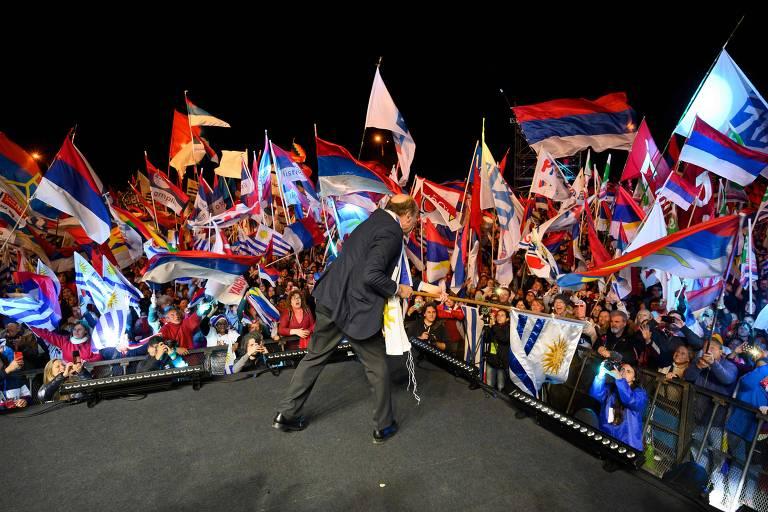 O candidato da Frente Ampla e líder nas pesquisas, Daniel Martínez, agita a bandeira do Uruguai durante comício em Montevidéu