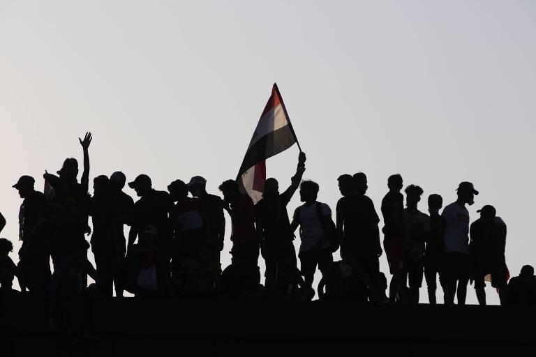 Manifestantes no topo de prédio na praça Tahrir, em Bagdá, capital do Iraque, neste sábado (26)