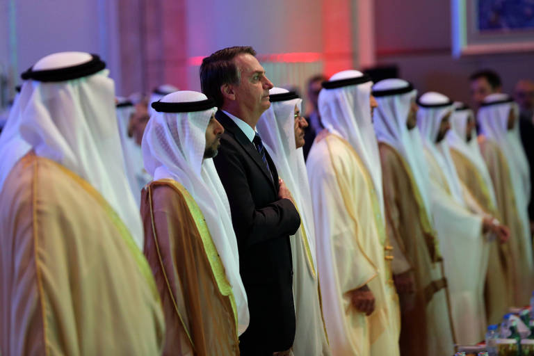 Presidente Bolsonaro, de terno preto, está em fileira com empresários árabes
