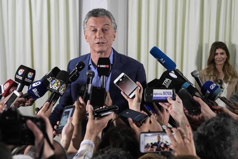 O atual presidente da Argentina e candidato à reeleição, Mauricio Macri, fala à imprensa após votar em Buenos Aires; ao fundo, a esposa de Macri, Juliana Awada