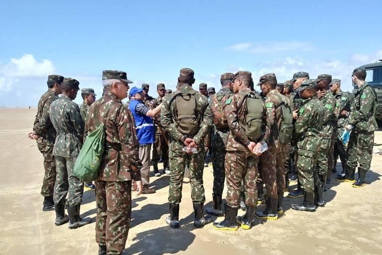 Homens do Exército recebem instruções de funcionários da Secretaria do Meio Ambiente de Aracaju para operação de limpeza do petróleo no litoral do Sergipe