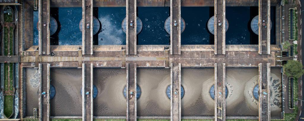 Vista aérea de dez tanques de tratamento de esgoto, com duas etapas: uma com água marrom e outra com água limpa