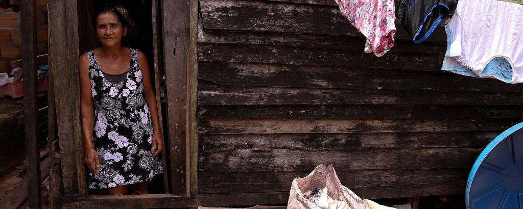 Mulher observa por janela de casebre, vista de fora, com varal e sacos de entulho