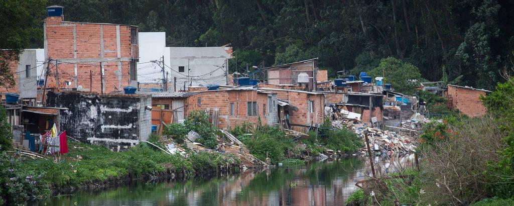 Vista de riacho repleto de lixo com casebres à margem
