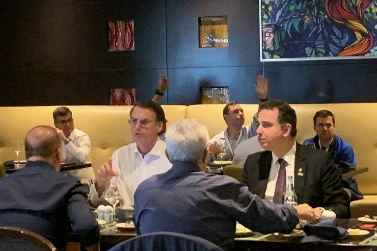 Bolsonaro, sentado à mesa em churrascaria