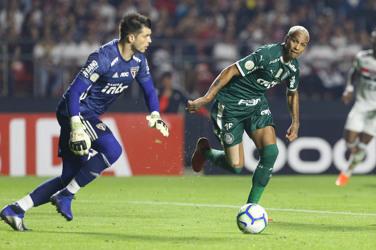 O palmeirense Deyverson tenta tomar a bola do goleiro são-paulino Tiago Volpi no duelo do primeiro turno do Brasileirão, que terminou empatado por 1 a 1