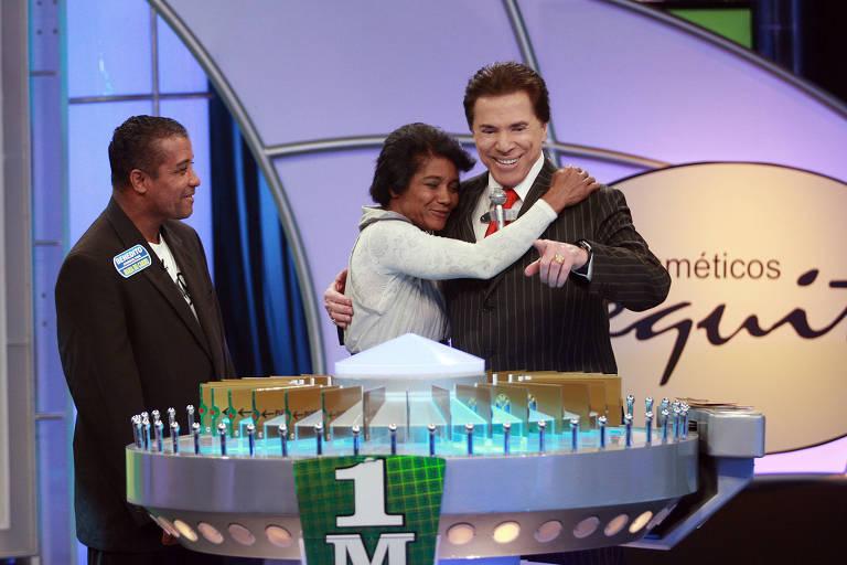 O empresário e apresentador Silvio Santos (dir.) abraça ganhadora durante programa Roda a Roda Jequeti, do canal SBT