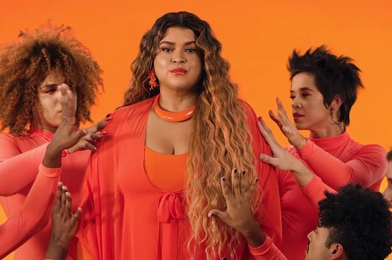Preta Gil veste a cor laranja, rodeada de dançarinos que também usam trajes na cor laranja