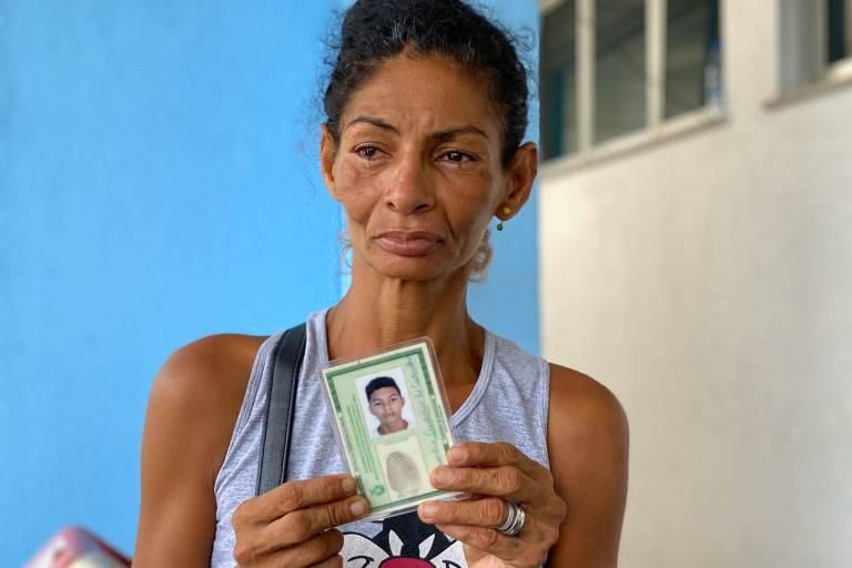 Christiane Custódio de Oliveira segura o RG de seu filho Alexsandro, 16, um dos 17 mortos pela PM na madrugada desta quarta-feira (30), em Manaus
