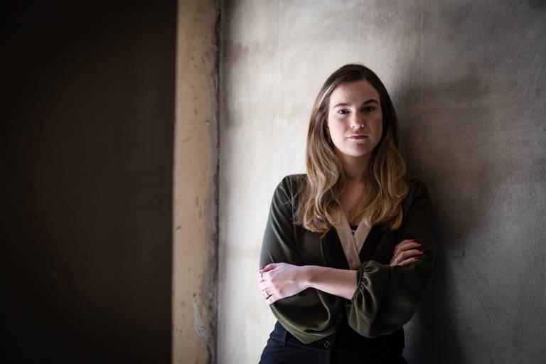 Mulher jovem de cabelos longos e loiros e camisa de manga longa verde recostada a parede cinzenta