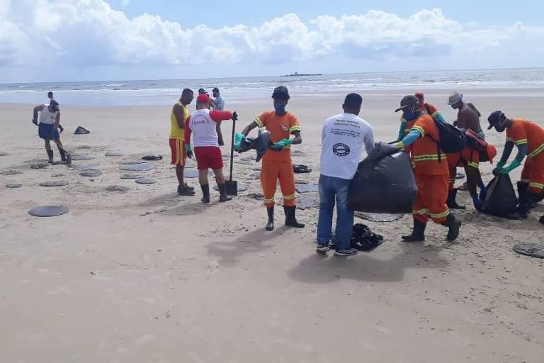 Funcionário e voluntários removendo manchas de óleo, Praia da Avenida, em Ilhéus