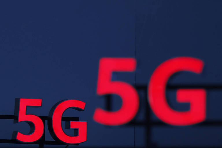 Logos 5G vermelhos são vistos iluminados durante uma conferência em Zurich. Os números se destacam ante o funo azul escuro.