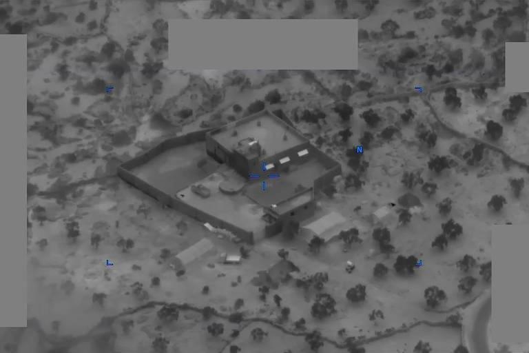 imagem aérea de baixa qualidade em preto e branco mostra espécie de casa no meio do deserto cercada por muros