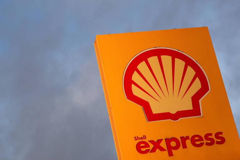 O logo da Royal Dutch Shell é visto em uma estação de petróleo laranja na Bélgica. Atrás, o céu nublado complementa a foto.
