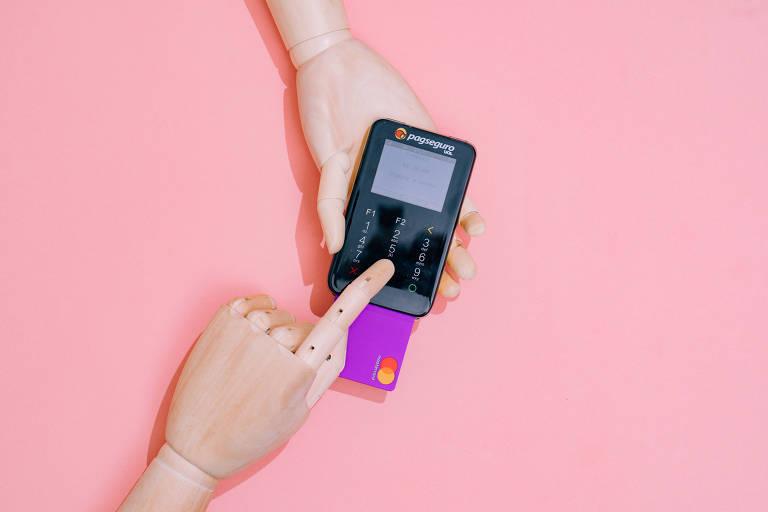 Still mostra mãos de madeira simulando usarem uma máquina de cartão