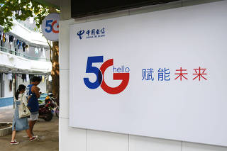 People holding their mobile phones walk past a China Telecom 5G sign at a university in Haikou