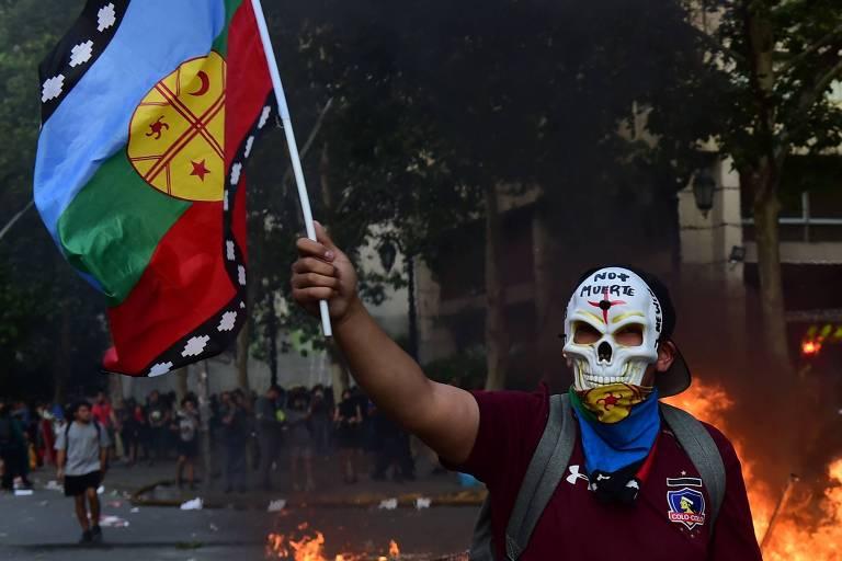 """Protestante com a camisa do Colo-Colo e uma máscara escrito """"sem mais mortes"""", durante as manifestações contra o presidente Piñera, no Chile"""