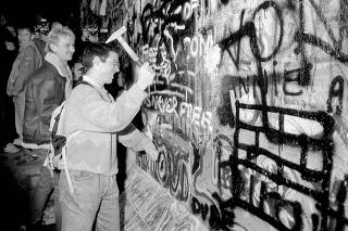 FILE PHOTO: A man hammers a section of the Berlin Wall near the Potsdamer Platz square after the opening of the East German border was announced in Berlin