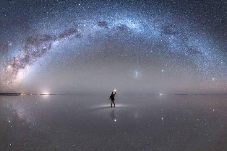 No céu muito estrelado se vê a via láctea, uma faixa azulada e brilhante que atravessa o céu como um arco-íris de estrelas. O deserto de sal reflete o céu. Uma pessoa se encontra no centro do quadro, parece caminhar nas estrelas.