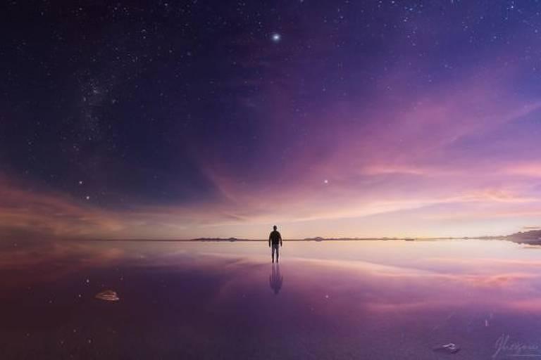 O crepúsculo faz o deserto e seu céu terem um tom roxo. Metade da imagem está já no escuro, enquanto a outra metade é brilhante.