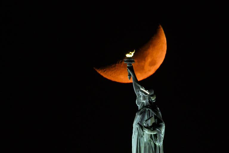 Lua pela metade, cor de laranja, passando por trás da estátua da liberdade