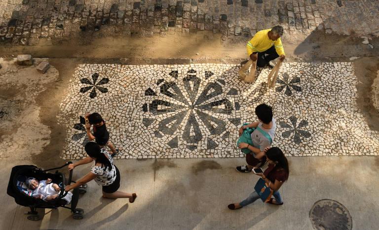 Calçada com desenho de flor é vista de cima, enquanto passam quatro pessoas
