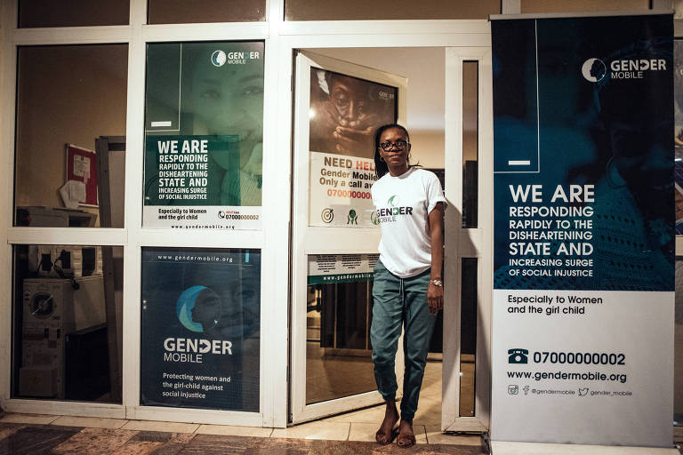 Omuwumi Ogunrotimi em frente a uma porta do gurpo de apoio