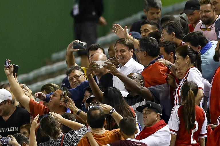O presidente Jair Bolsonaro com torcedores do Paraguai no estádio Bezerrão, em Brasília, que ficou esvaziado no jogo do país contra a Itália pela Copa Sub-17